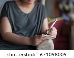 left handed woman writing some... | Shutterstock . vector #671098009