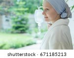 Small photo of Woman in white robe smiling and looking out the window