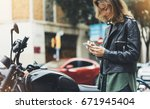 girl in leather jacket holding... | Shutterstock . vector #671945404