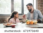 portrait of father feeding... | Shutterstock . vector #671973640