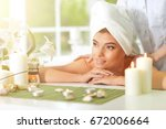 girl lying down on a massage bed | Shutterstock . vector #672006664