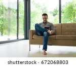 young happy man on sofa using... | Shutterstock . vector #672068803