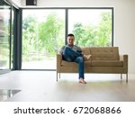 young happy man on sofa using... | Shutterstock . vector #672068866