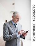 businessman typing on handheld   Shutterstock . vector #672082780