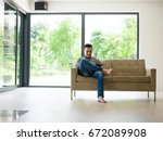 young happy man on sofa using... | Shutterstock . vector #672089908