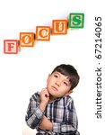 A concept image of a young boy under the word blocks that says focus. - stock photo