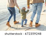family on a walk by the water.  ... | Shutterstock . vector #672359248