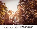 happy family in nature. parents ... | Shutterstock . vector #672450400