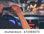 man drink beer while driving at ... | Shutterstock . vector #672483073