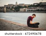 young man sitting on the danube ... | Shutterstock . vector #672490678