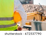 Small photo of engineer holding yellow helmet for workers security on background of new highrise apartment buildings and construction cranes on background of evening sunset cloudy sky Silhouette Crane lifts load