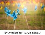 paper windmills in green grass... | Shutterstock . vector #672558580