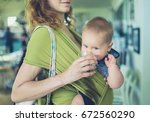 a young mother is giving her... | Shutterstock . vector #672560290