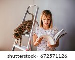 woman reads a book while bengal ... | Shutterstock . vector #672571126
