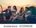 friends on beach in sunset | Shutterstock . vector #672598558