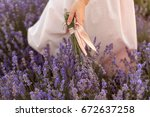 Stock photo woman touching lavender in the field on sunset 672637258