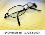 glassed on yellow notepad in... | Shutterstock . vector #672656434