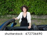 happy forties woman standing next to car outside house