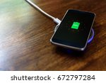 smartphone charging on a... | Shutterstock . vector #672797284