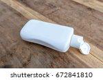 a white bottle on wood... | Shutterstock . vector #672841810