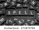 "Small photo of Black letter tiles spelling the word ""spell"" on a reflective background"