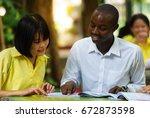 american teacher teaching asian ...   Shutterstock . vector #672873598