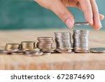 hand put coin to money ... | Shutterstock . vector #672874690