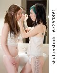 two young woman in lingerie applying makeup - stock photo