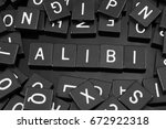 """Small photo of Black letter tiles spelling the word """"alibi"""" on a reflective background"""