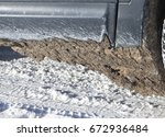 Small photo of dirty snow adhered to the car while driving on the winter road