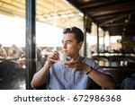 asian men relax with coffee in... | Shutterstock . vector #672986368