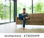 young happy man on sofa using... | Shutterstock . vector #673020499