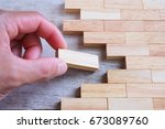 Small photo of Man finger put a wood block to complete and finish wood block in line,symbolizing joining team or making unity teamwork,successful,or completion.