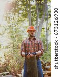 Small photo of Portrait of a bearded logger in a helmet with a log