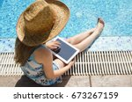 child girl sitting by the pool... | Shutterstock . vector #673267159