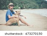 Stock photo young handsome man wearing blue t shirt hat and sunglasses sitting on the beach with the dog in 673270150