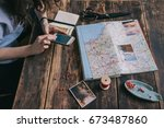young woman plans trip on map... | Shutterstock . vector #673487860