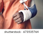 Small photo of Closeup midsection of a man with broken arm in cast