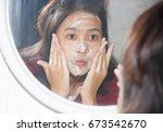asian woman face wash with foam ... | Shutterstock . vector #673542670