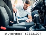 man cleans car interior with... | Shutterstock . vector #673631074