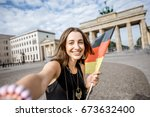 Young woman tourist making selfie photo with german flag standing in front of the famous Brandenburg gates in Berlin