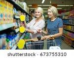 two smiling women purchasing... | Shutterstock . vector #673755310