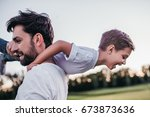dad and son having fun outdoors. | Shutterstock . vector #673873636