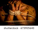 Small photo of A young man with tied up and locked with rope in the abandoned building, Infringement hostage and the anti Human Trafficking concept.