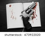 Revolver And A Open Notebook I...