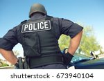 rear view of policeman in... | Shutterstock . vector #673940104