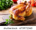 whole roasted chicken on a... | Shutterstock . vector #673972360