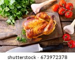 whole roasted chicken on a... | Shutterstock . vector #673972378