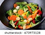 stir fried vegetables in a wok... | Shutterstock . vector #673973128