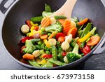 Small photo of stir fried vegetables in a wok on dark table